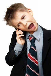 Boy In Suit Yelling Into Cellphone over white background